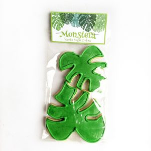 Two sugar cookies shaped as monstera leaves