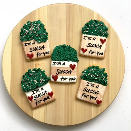 This is a picture of five cookies shaped as succulents with the text I'm a succa for you written on the pot.